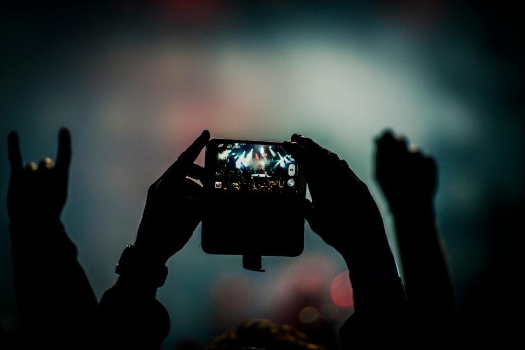 Spectateur filmant un concert avec un smartphone