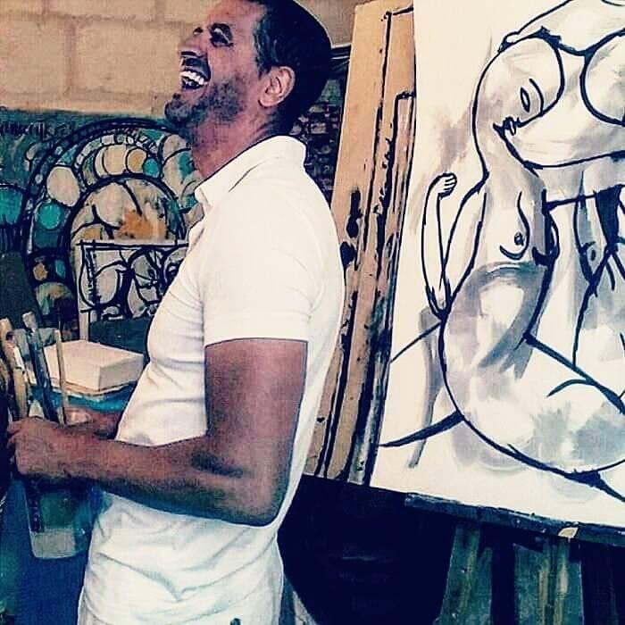 Moho devant une de ses œuvres