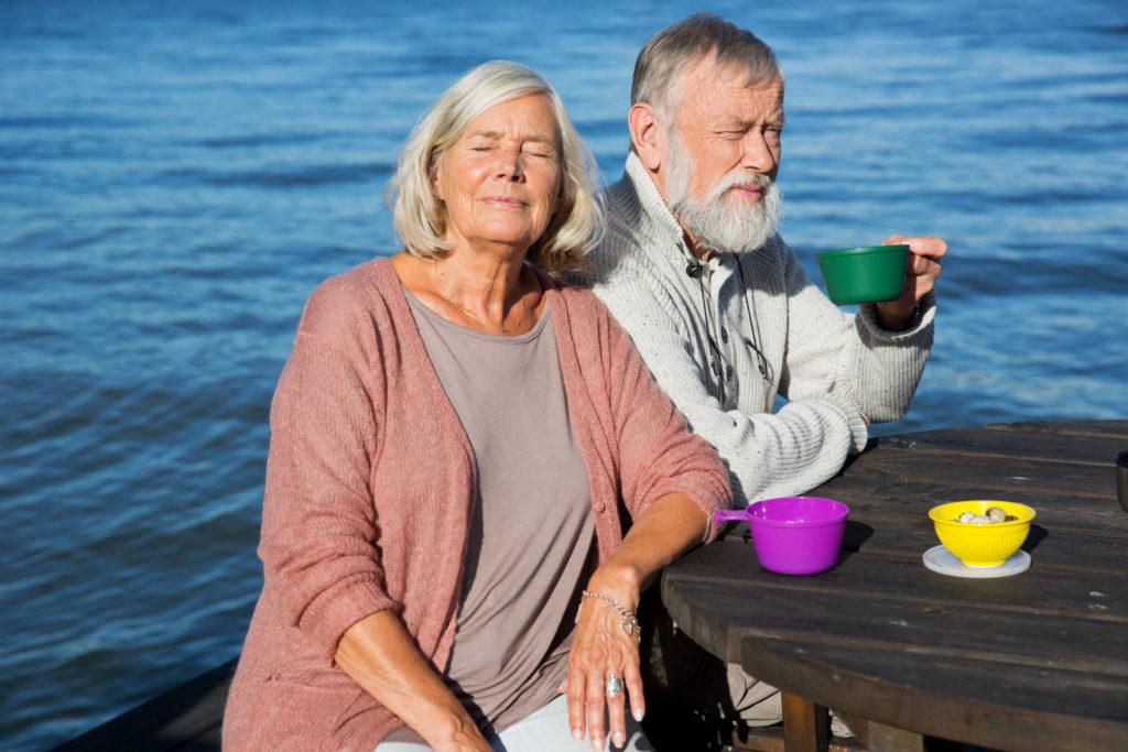 Couple de retraités mangeant au bord de l'eau