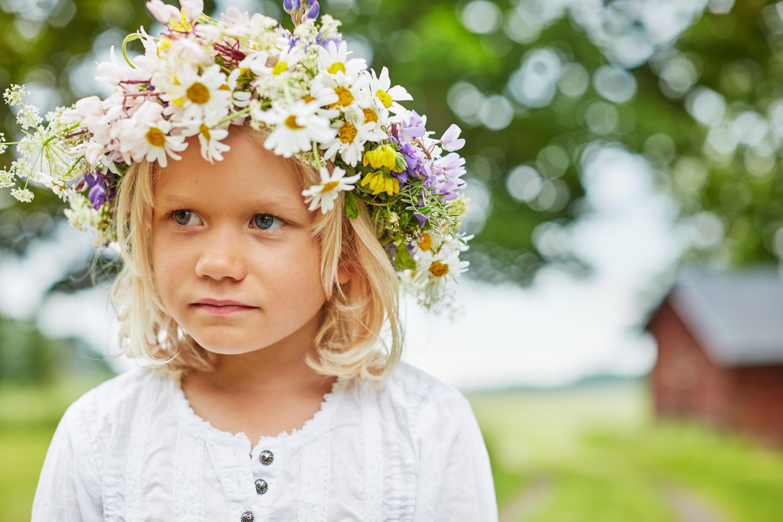 Petite fille avec une couronne de fleurs de midsommar